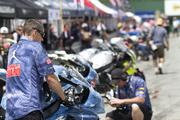 Motorcyclists' crews prep the bikes for races in the pit area at Mid-Ohio.