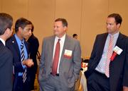 Matt Snow, center, and Rick Paden, right, with Dixon Hughes Goodman, have a chat with attendees.