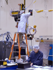 Satellite manufacturing technicians and engineers work on assembly of a large telecommunications satellite.