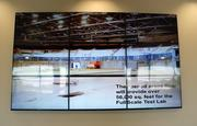 A video board inside NIAR's Kansas Coliseum space plays a slideshow of renovation pictures.