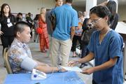 From left, Jeremy Yasutake  gets a blood pressure reading by Tabitha Dudoit.