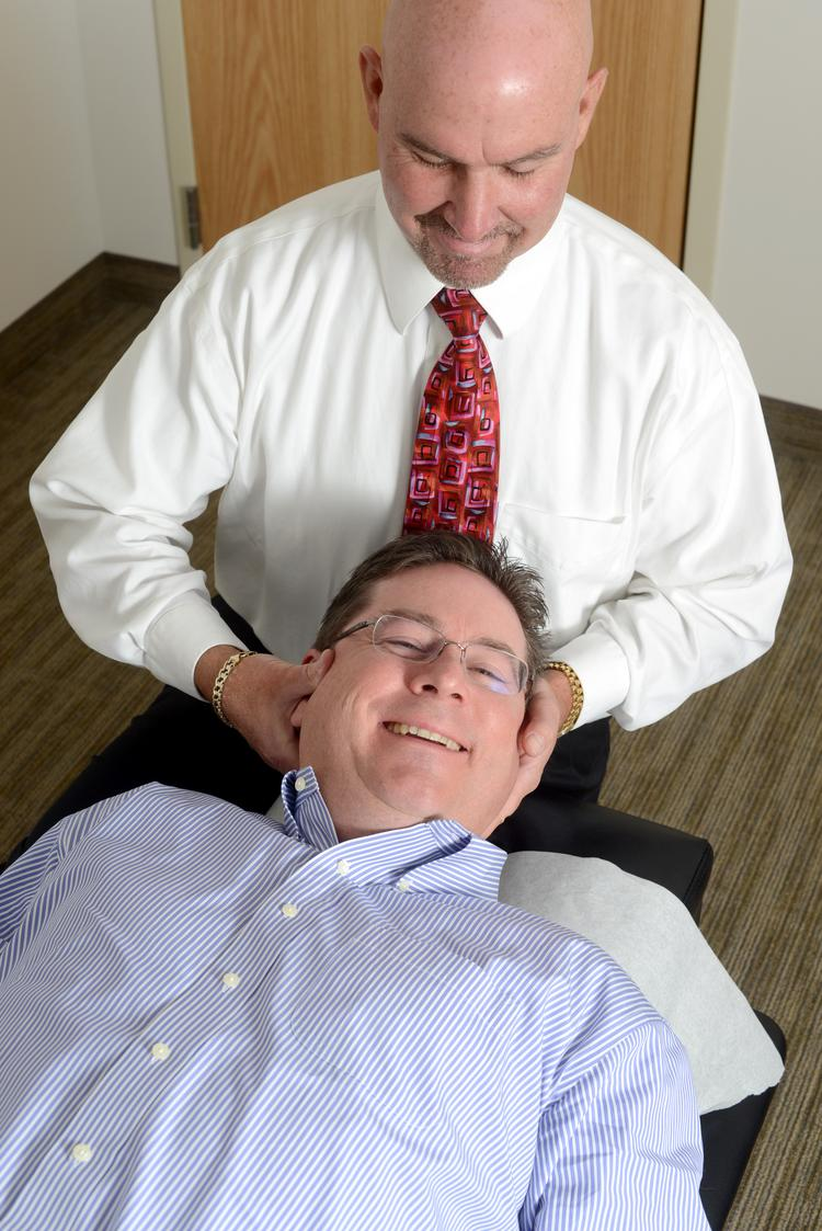 Kevin Kelly, EVP of Summit Community Bank, at the hands of chiropractor Larry Estebo, co-owner of Premier Health Chiropractic.