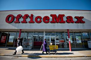 Shoppers walk outside an OfficeMax Inc. store. OfficeMax is rumored to be interested in a merger with rival Office Depot.