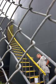 Corey Pine paints one of 12, one million-gallon tanks holding highly refined base oil at the port.
