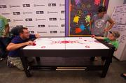 Actor and Overland Park native Rob Riggle plays air hockey with liver transplant patient Bryson Comfort, 4, at Children's Mercy Hospital.