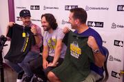 Actor and Overland Park native Jason Sudeikis (left) compares his Shawnee Mission West T-shirt with Rob Riggle's Shawnee Mission South T-shirt (right) during a press conference on the upcoming Big Slick Poker Tournament, which is a Children's Mercy Hospital fundraiser. Paul Rudd (center) was presented a Shawnee Mission West T-shirt earlier.