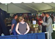 NYRA President and CEO Christopher Kay, right, in gray, talks to those working at the booth for SpaceyTracey's Pickles on Sunday at the Uniquely New York Marketplace at Saratoga Race Course.