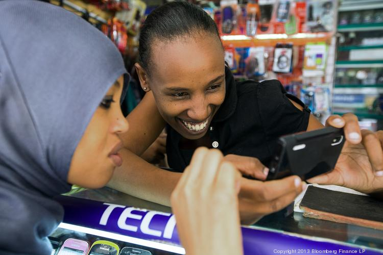 An employee demonstrates a mobile handset to a customer at the counter of a phone store in Nairobi, Kenya. Over the weekend, Facebook announced its most basic mobile software, Facebook for Every Phone, is now being used by 100 million people worldwide.