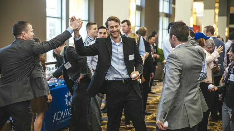 Attendees of the Kansas City Business Journal's 2015 Best Places to Work high five each other.