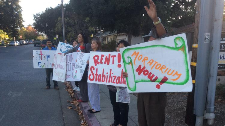 Advocates with the Mountain View Tenants Coalition make their views known outside the Mountain View Senior Center before a city council meeting.