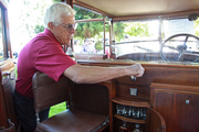 Craig Hannum raises the window divide in the back and front of his 1926 Rolls Royce making his built-in bar road legal
