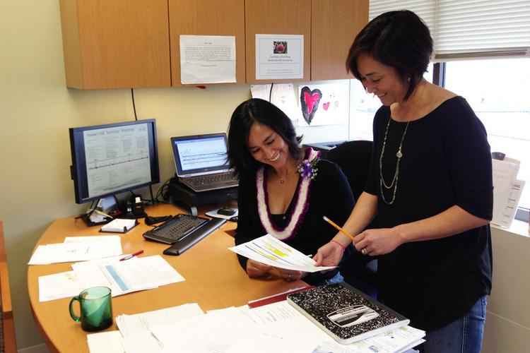 Christine Sakuda, left, executive director of the Hawaii Health Information Exchange, confers with Holly Iwasaki, communication and outreach specialist for the nonprofit.