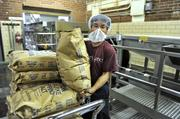 A worker prepares to add salt to the baking process at the Snyder's-Lance Inc. facility in Charlotte.