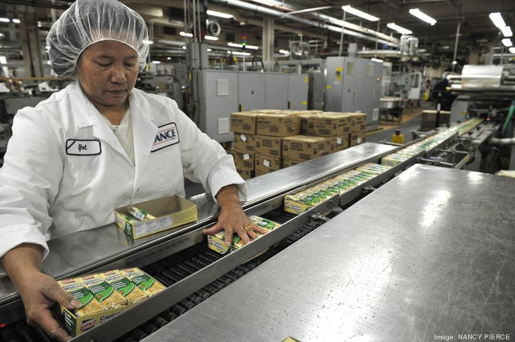 A worker at the Snyders-Lance Inc. bakery in Charlotte inspects the packaged crackers on a conveyor belt before they are shipped.