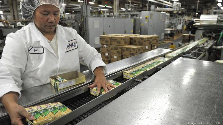 A worker at the Snyder's-Lance Inc. bakery in Charlotte, N.C., inspects packaged crackers on a conveyor belt before they are shipped.
