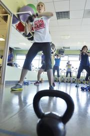 Greta Olson takes part in Amgen's kettlebell class in their onsite gym. The company was the No. 5 Healthiest Employer for 2013 in the large business category.
