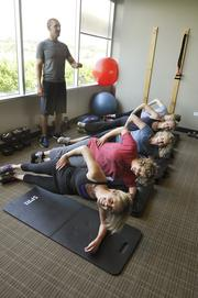 A group works out with a personal trainer at Colorado Health. The company was the No. 3 Healthiest Employer for 2013 in the medium-sized business category.