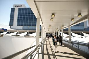 People travel along a walkway at the Grand Hyatt Hotel at the Dallas-Fort Worth International Airport. Unlike other hotel chains, Hyatt has largely resisted cutting back on its Gold Passport loyalty program.