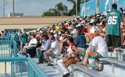 Fans watch the Miami Dolphins practice at the Doctors Hospital Training Facility in Miami.