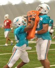 Running backs Marcus Thigpen and Evan Rodriguez go to it during a drill.