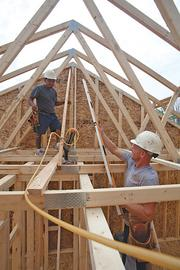 Justin Meade, foreground, and Fidel Pablo, who work for Todd Homes, are framing a house on Ashlyn Court in Liberty Twp.