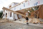 Andy Morath of Todd Homes carries lumber from the garage as he works on a house on Ashlyn Court in Liberty Twp.