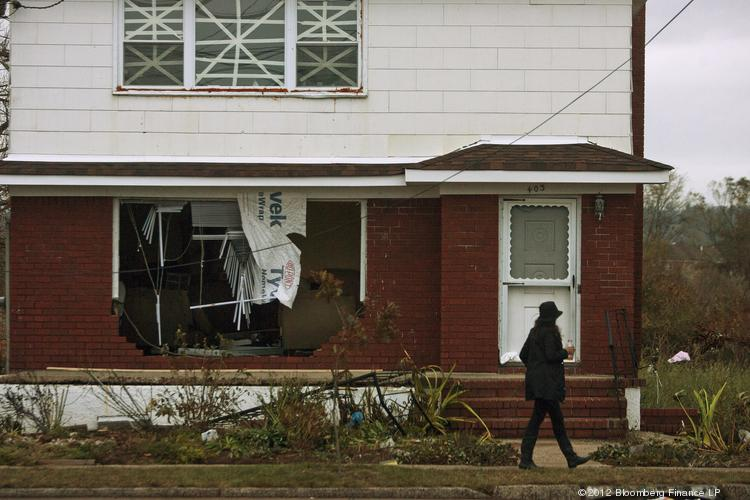 A woman walks past a damaged house on Staten Island.