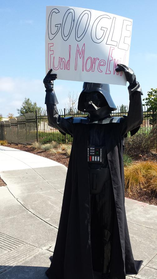 A protester holds a sign outside Google headquarters, militating against the search giant's support of Sen. James Inhofe, a noted climate change denier and opponent of the environmental movement.