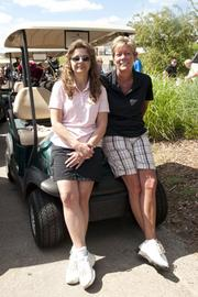 (From left) Anne Frischmann and Stacey Newman hanging out by the golf carts before the shotgun start.