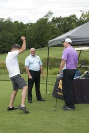 Golfers visit the Abra Auto Body and Glass-sponsored hole.