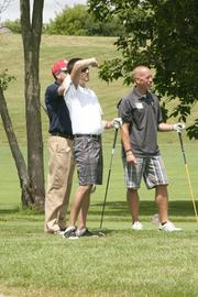 Golfers from the InvestorsBank foursome admire a long drive.