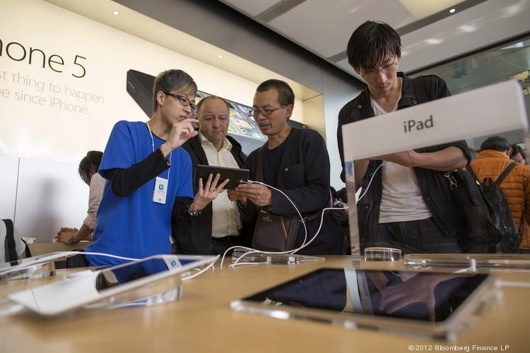 Chinese customers shop at an Apple store in Hong Kong. The company this week issued a warning about counterfeit iPhone and iPad chargers, after a woman in China was fatally electrocuted while using a fake charger.