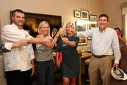 Inside a model room, a champagne toast after the tour. Executive Chef Chad Johnson, Facebook contest winner Kristen McKinlay Manno, contest winner Rachel Slowey and General Manager Tom Haines.