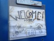 A handwritten welcome sign inside the door giving the names for both companies.