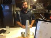 T.J. Fairchild stands behind the counter of Commonwealth Coffee Co.