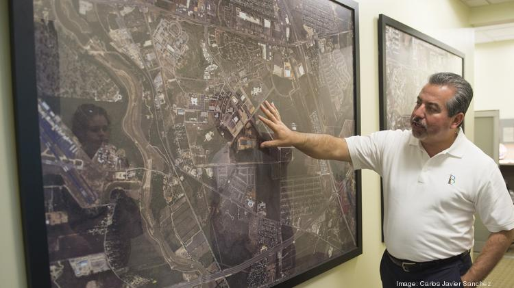 Brooks City Base President and CEO Leo Gomez surveys an aerial map of the former Air Force base site.