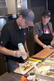 Chris Obligato, an operations consultant for KFC eleven, assembled one of the new flatbreads offered as Jessica Williams, product development manager for KFC, watched.