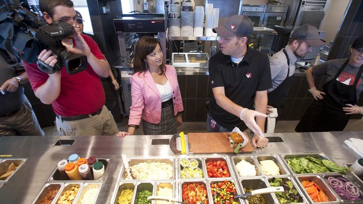 Chris Obligato, operations consultant for KFC 11, described the food assembly process to WDRB reporter Valerie Chinn and photographer Chris Monroe when the restaurant opened in Louisville. ​Taco Bell Corp. is planning to open a similar fast casual restaurant in Huntington Beach, Calif. this summer.