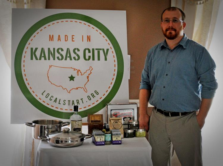 Local Start founder Richard Shipley stands with the logo his organization designed to designate locally made products.