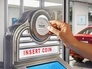 The customer then inserts a Carvana-branded coin into the custom coin slot to start the vending process.