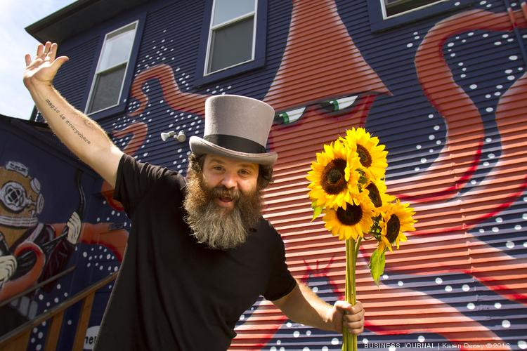 "Ryan Henry Ward, an artist who specializes in murals and canvas paintings, is photographed in front of a mural he did at Dive Commercial International in Seattle. Ward describes his work as ""magical pop surrealism"" and receives commissions from businesses, schools and individuals to help brighten interior and exterior spaces and provide an effervescent ""hip and cool"" look to their business. His client list ranges from the Fred Hutchinson Cancer Research Center to banks to pet portraits."