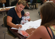 Lisa Sedlar, CEO and Founder of Green Zebra Grocery, cradles a visiting infant during a vendor fair for Portland's newest convenience chain. Green Zebra opens its first store Sept. 25 in Portland's Kenton neighborhood.