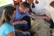 Joey Brown shows Maddie Porter the fine art of milking a cow.