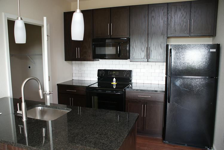 A typical kitchen, which includes granite countertops. Note the pantry to the left, which can house a washer/dryer on one side and food on the other.