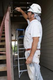 Victor Ayala of Atlas Painting in Wichita paints exterior railings Friday.