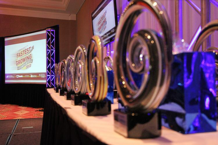 A close-up of the honoree awards lined up on the stage