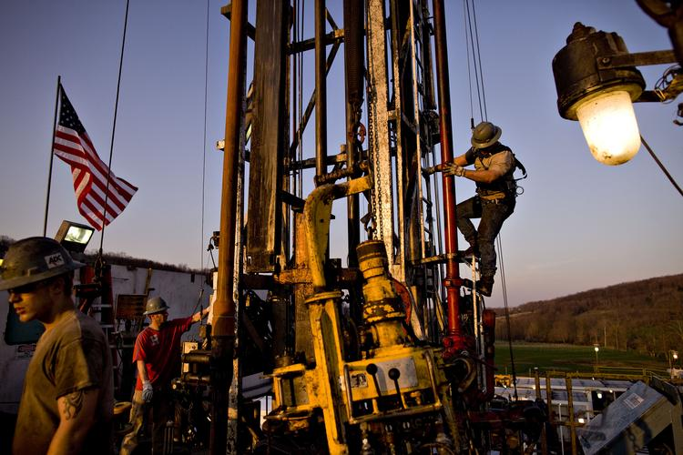 Nomac Drilling Corp. derrick man Justin Spruell, right, climbs down from an overhead platform after connecting a section of drill pipe on a Chesapeake Energy Corp. natural gas drill site in Bradford County, Pa.