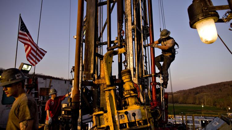 Derrick worker Justin Spruell, right, climbs down an overhead platform after connecting a section of drill pipe on a Chesapeake Energy natural gas drill site. Chesapeake's board approved the spinoff of the company's oilfield services unit as Seventy Seven Energy Inc.