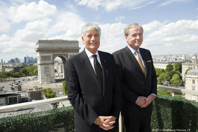 Maurice Levy, CEO of Publicis Groupe, left, and John Wren, CEO of Omnicom Group, pose for a photograph after signing the merger during a news conference held on the rooftop of the Publicis headquarters in Paris.