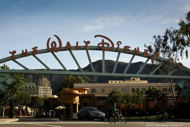 A man rides a bicycle past the entrance to The Walt Disney Co. studios in Burbank, Calif.